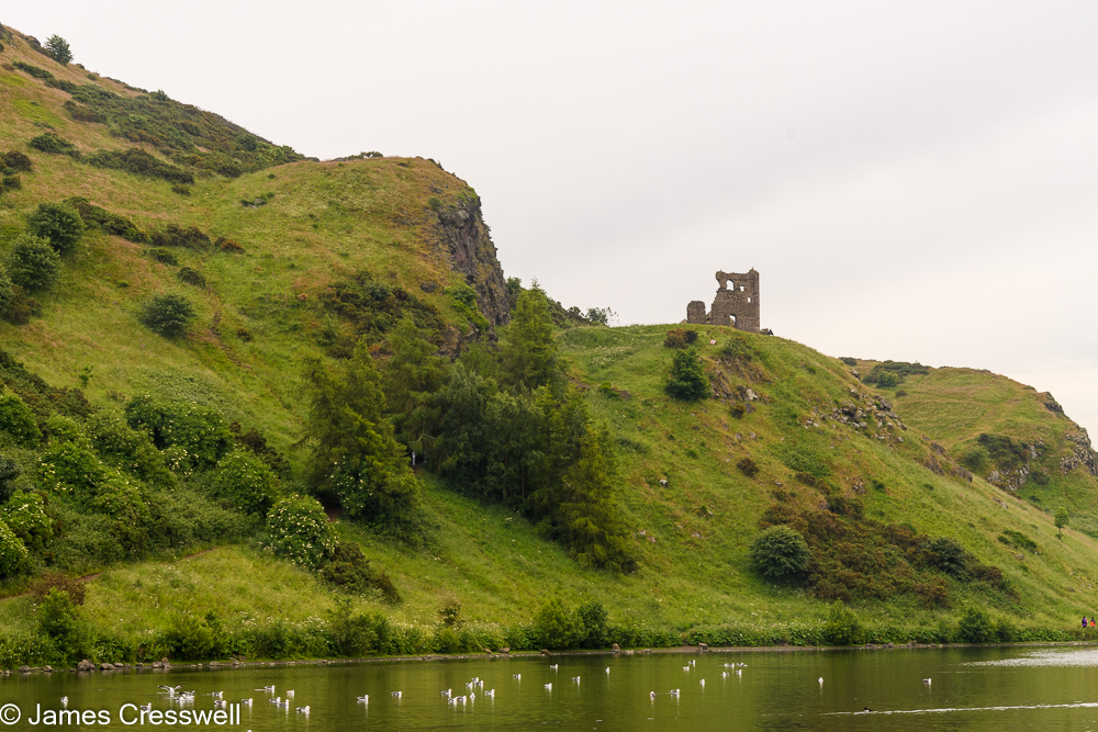 A ruined castle on a rocky hill, with a lake in the foreground