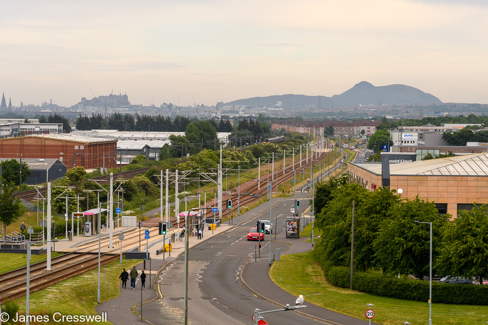 A tramline in the foreground with mountains and a city sky line in the background