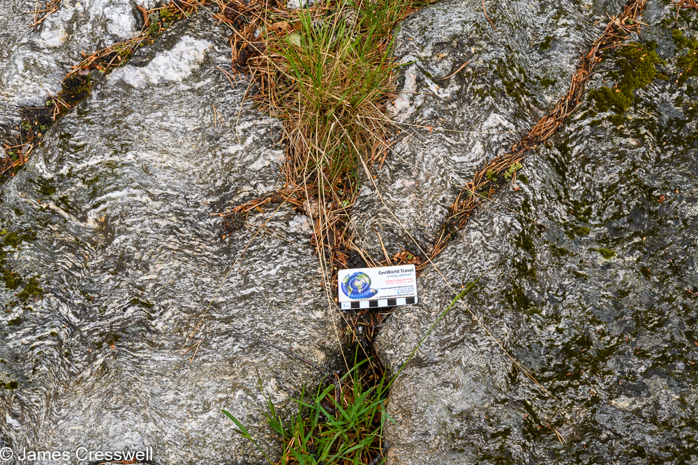 A scale card placed on top of rocks which contains wavy white bands