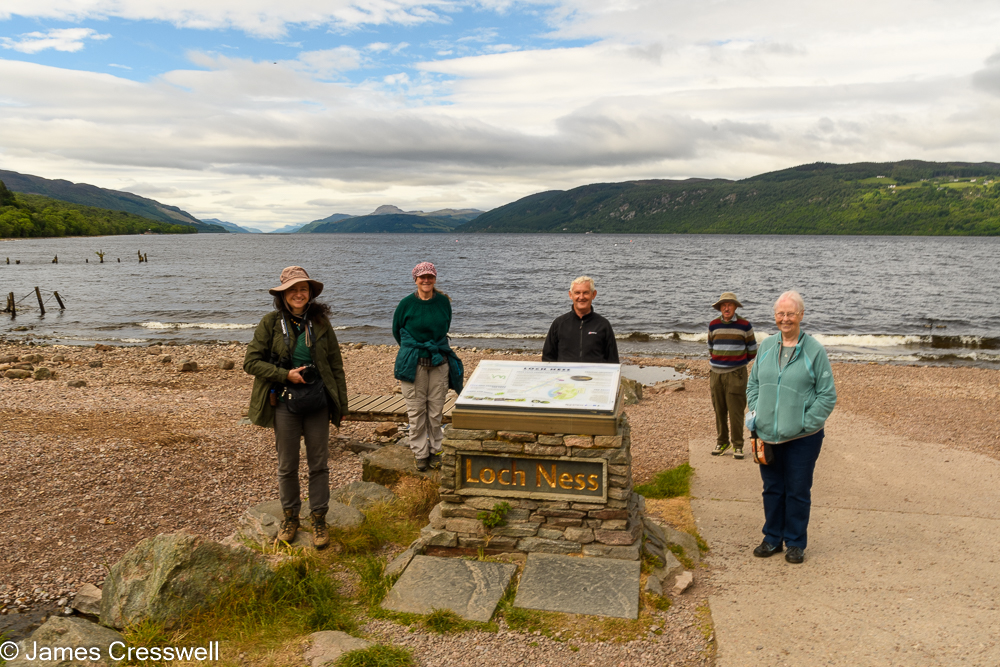 Five people stand next to a sign in front of a large lake