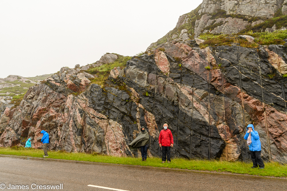 Five people stand in front of a colourful rocks in a road cutting