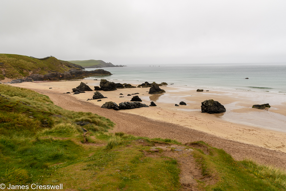 View over a sandy beach that contains rocky outcrops