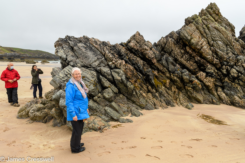 Three people standing next to a rocky outcrop on a sandy beach