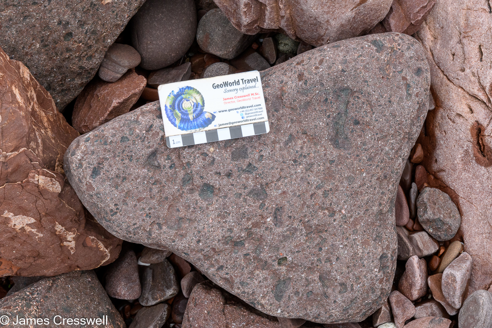 A scale card on top of a rock rock that contains green fragements